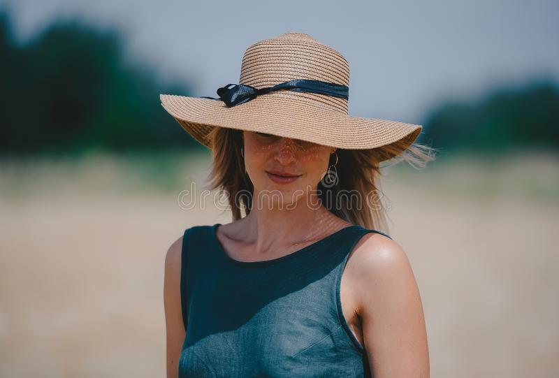 Femme dans un chapeau de paille qui cache ses yeux dans la perspective de la nature images libres de droits