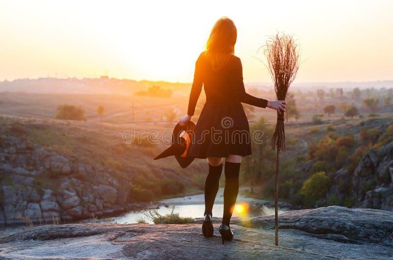 Femme dans un costume de sorcière avec un balai et un chapeau, un fond de h photo stock