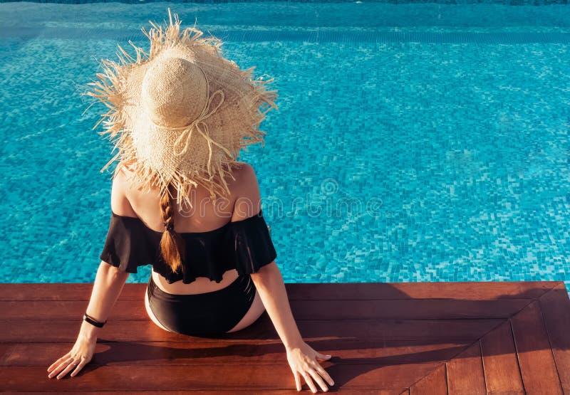 Femme dans un grand chapeau de paille se reposant près de la piscine appréciant le soleil image stock