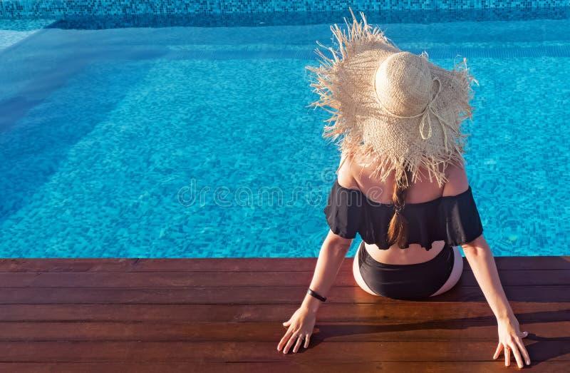 Femme dans un grand chapeau de paille se reposant près de la piscine appréciant le soleil image libre de droits