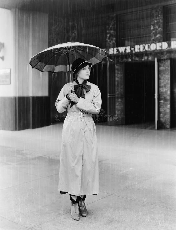 Femme dans un imperméable et parapluie (toutes les personnes représentées ne sont pas plus long vivantes et aucun domaine n'exist images libres de droits
