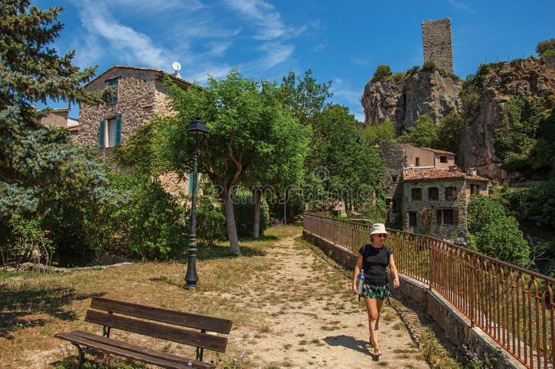 Femme dans un jardin avec des arbres, des maisons et la falaise dans Chateaudouble photographie stock