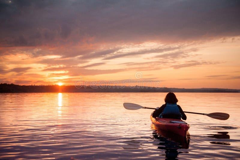 Femme dans un kayak sur la rivière sur le coucher du soleil scénique photographie stock