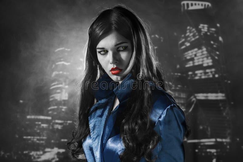 Femme dans un manteau bleu avec les lèvres rouges noires et blanches dans la ville o photo libre de droits