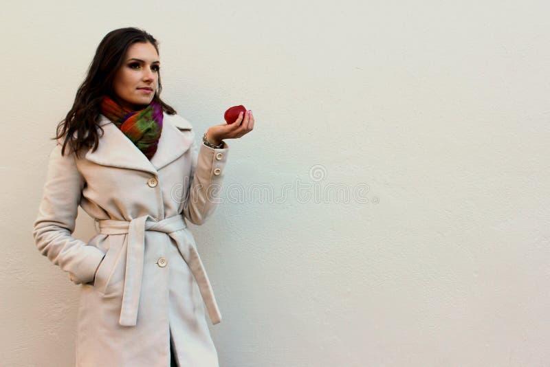 Femme dans un manteau tenant une pomme juteuse rouge mordue images stock