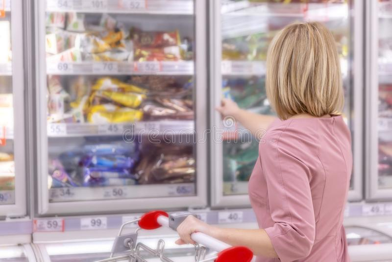 Femme dans un supermarché dans le département d'aliments surgelés Plan rapproch? photographie stock