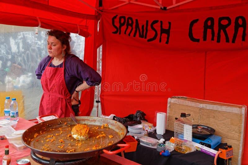 Femme dans un support de nourriture sur le marché de ruelle de brique photo libre de droits