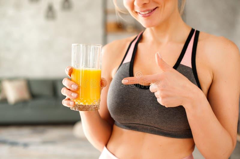 Femme dans un survêtement buvant du jus d'orange photo libre de droits