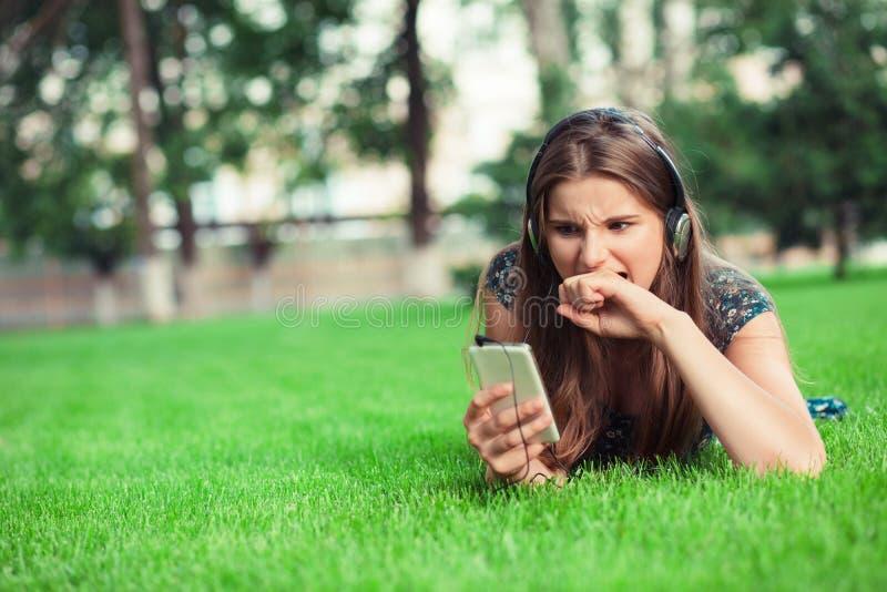 Femme dans une frustration d'horreur mordre son poing regardant l'écran de téléphone dehors image stock