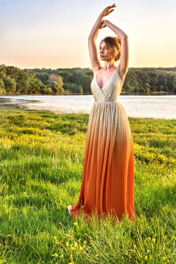 Femme dans une longue robe fascinante au coucher du soleil Belle robe de gradient de fille Belle vue d'horizontal Modes chaudes d photographie stock libre de droits