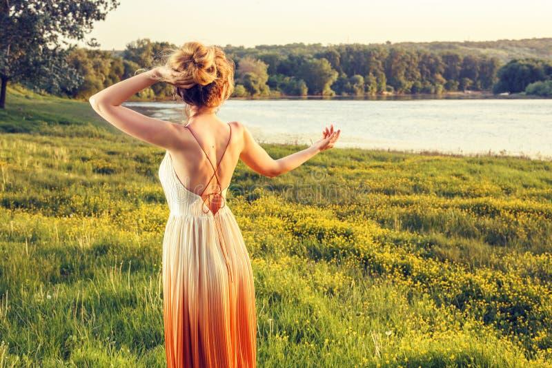 Femme dans une longue robe fascinante au coucher du soleil Belle fille Belle vue de paysage, tir du dos photos stock