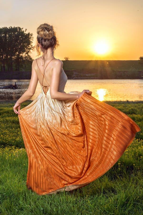 Femme dans une longue robe fascinante au coucher du soleil Belle vue de paysage, tir du dos images stock
