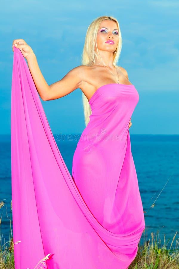 Femme dans une longue robe rose. photos stock