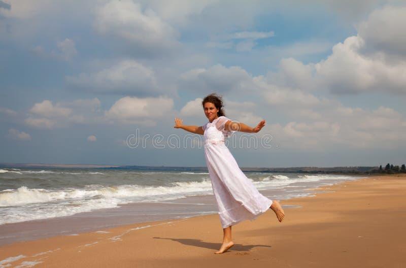 Femme dans une robe blanche sur la côte d'océan photographie stock libre de droits
