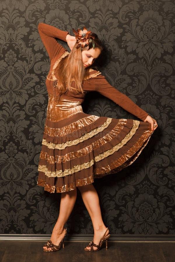 Femme dans une robe brune restant près d'un mur photographie stock