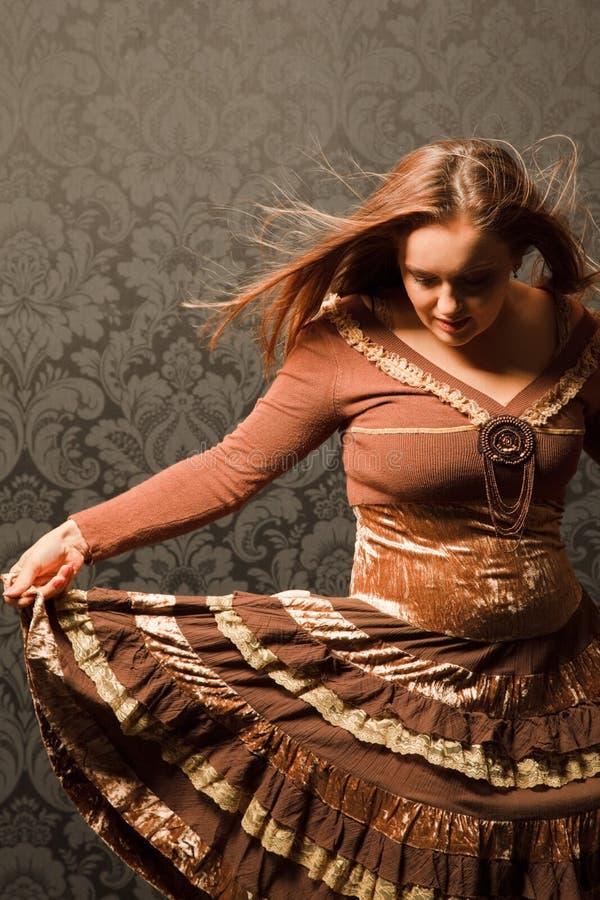 Femme dans une robe brune restant près d'un mur photos libres de droits
