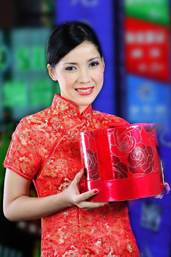 Femme dans une robe chinoise recevant un cadeau photographie stock libre de droits