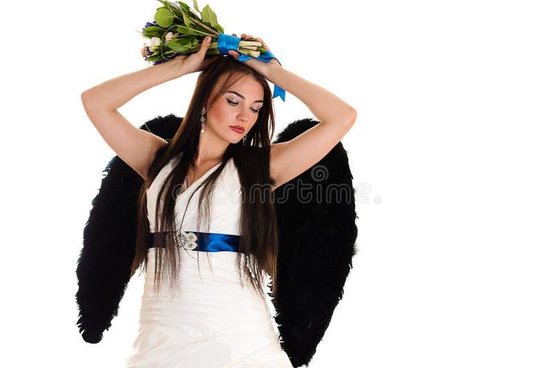 Femme dans une robe de mariage avec les ailes noires photo stock