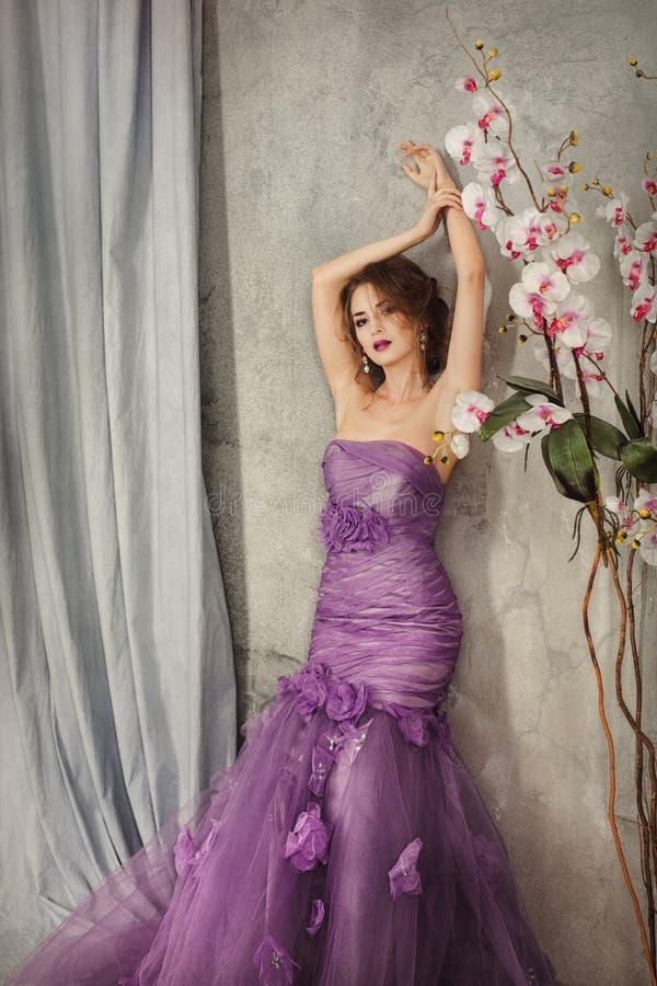 Femme dans une robe lilas se tenant près du mur avec des fleurs photos stock