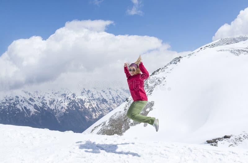 Femme dans une veste rouge sautant sur un fond des montagnes neigeuses, hiver dans les montagnes, les rires de fille photos libres de droits