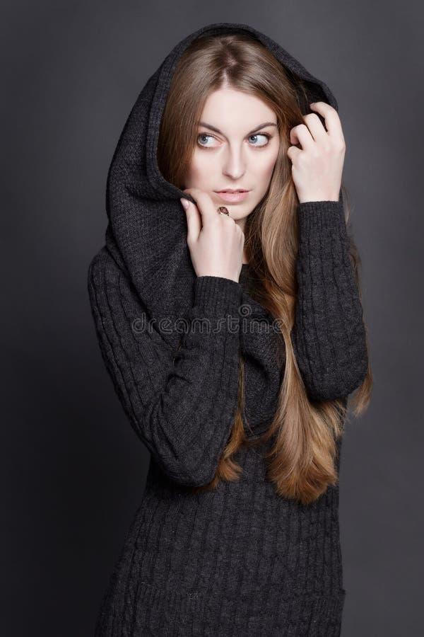 Femme de Иeautiful avec de longs, magnifiques cheveux blonds foncés Elle est habillée dans la robe grise chaude de knit avec un  photos stock