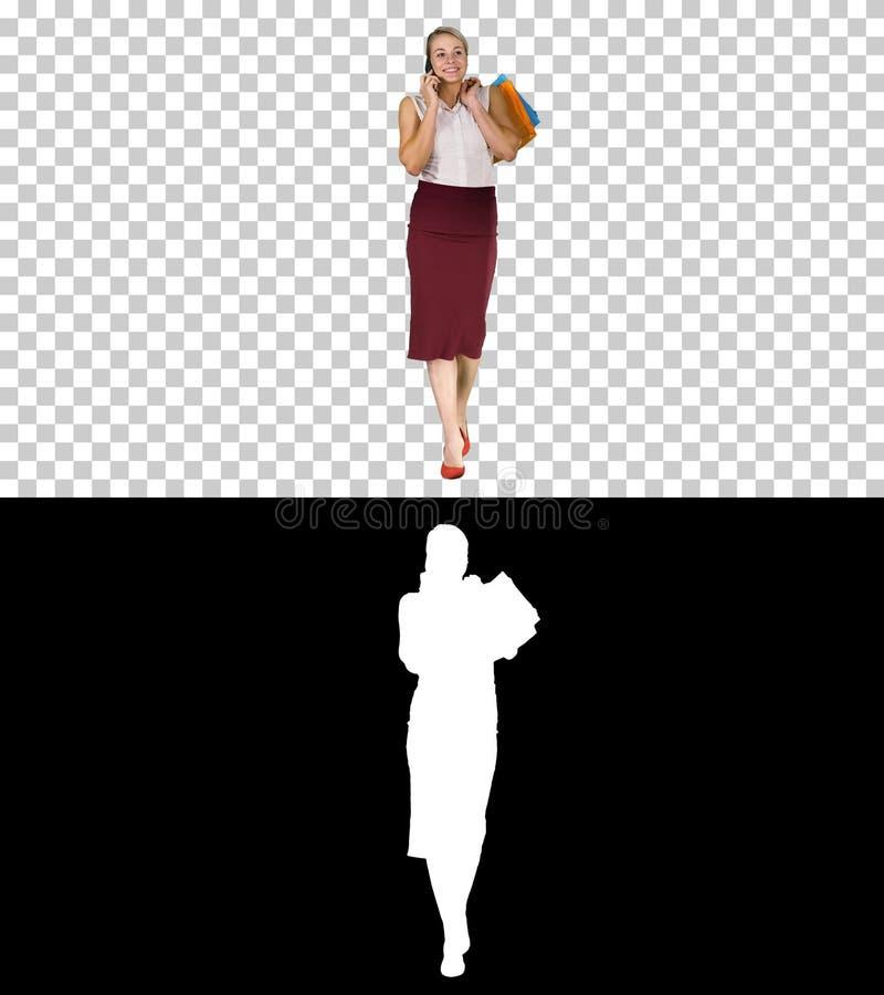 Femme de achat avec des sacs parlant au téléphone, Alpha Channel images stock