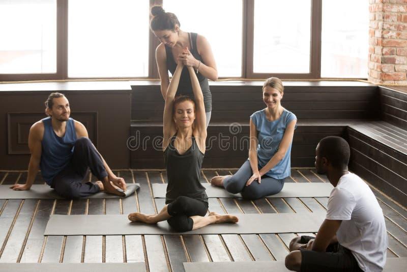 Femme de aide d'instructeur féminin pour étirer l'enseignement au tra de groupe image stock