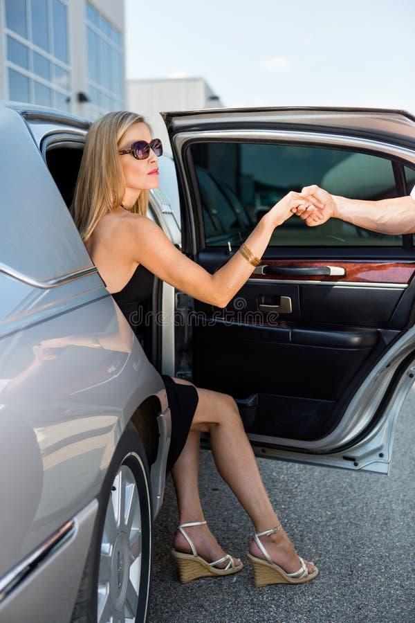Femme de aide de la main de l'homme faisant un pas hors de la voiture images libres de droits