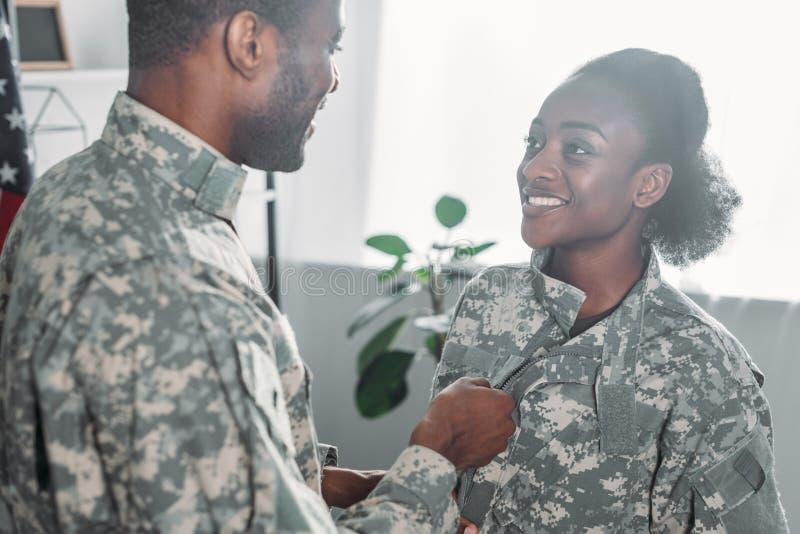 Femme de aide de soldat masculin à obtenir habillée photographie stock