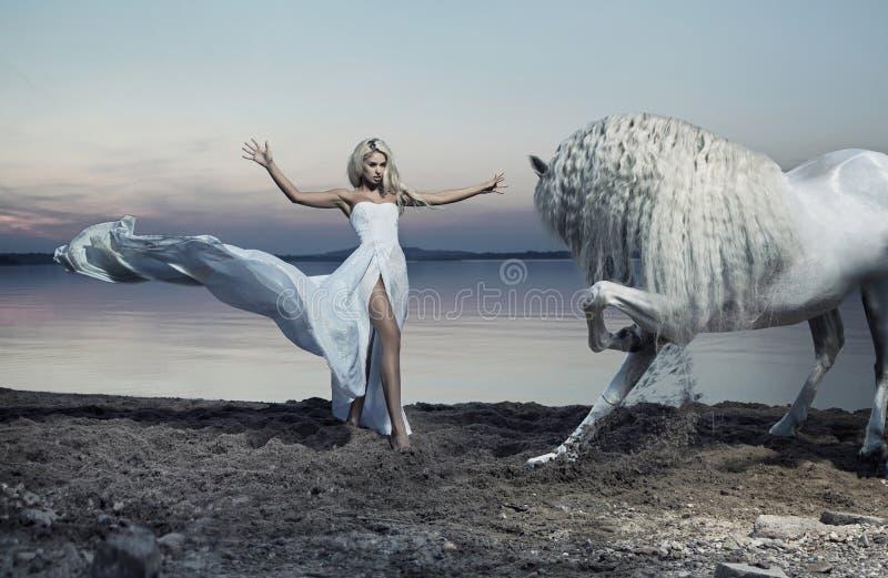 Femme de attirance apprivoisant le cheval photo stock