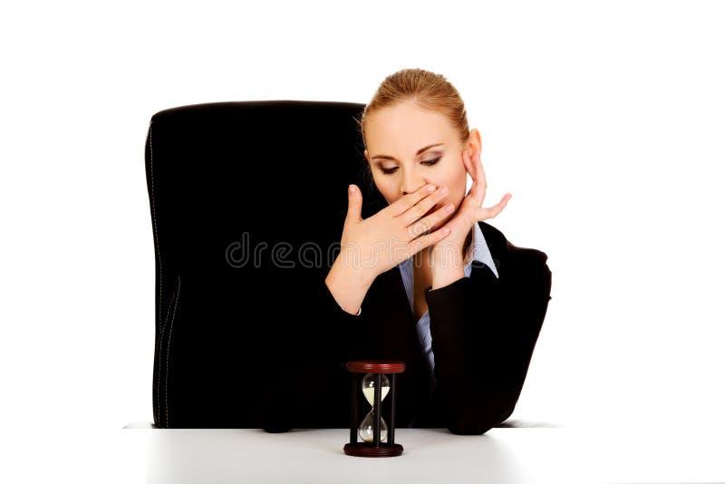 Femme de baîllement d'affaires avec le sablier sur le bureau photo stock