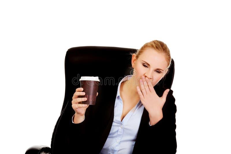 Femme de baîllement d'affaires s'asseyant sur le fauteuil roulant et tenir la tasse de café photo libre de droits