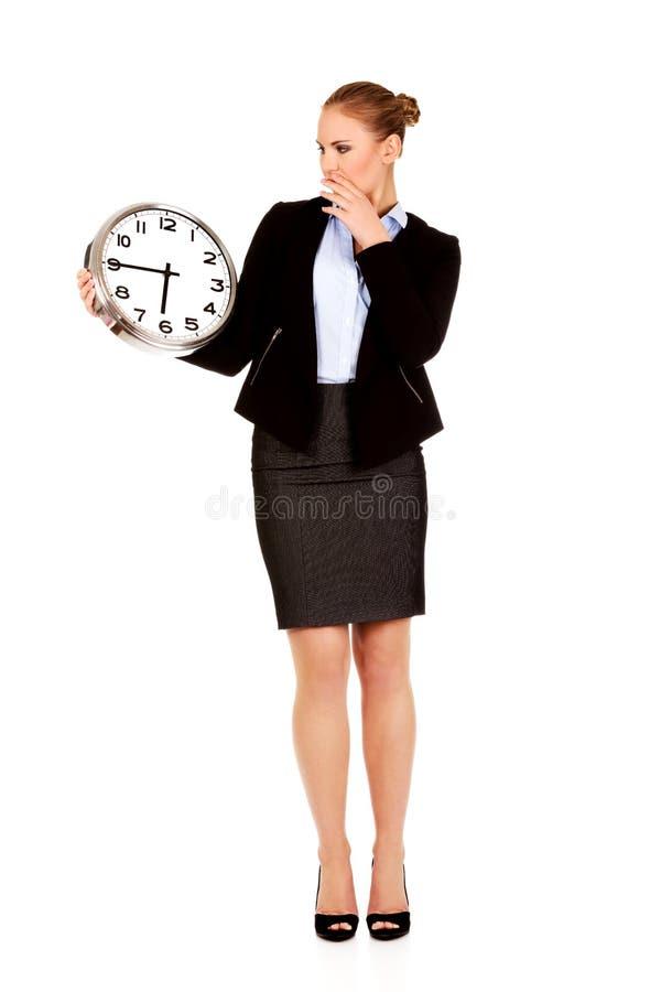 Femme de baîllement d'affaires tenant l'horloge de bureau photo stock
