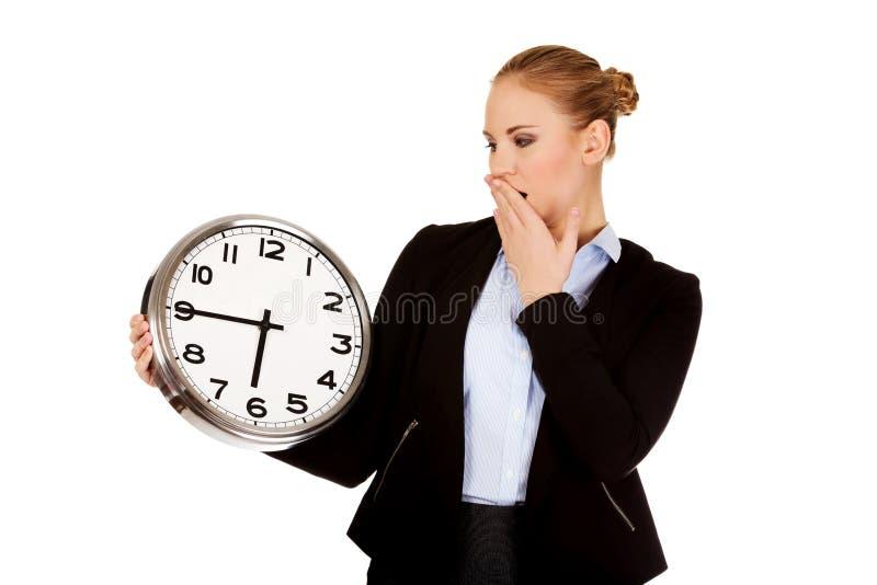 Femme de baîllement d'affaires tenant l'horloge de bureau image stock