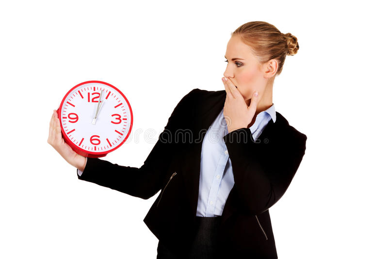 Femme de baîllement d'affaires tenant l'horloge de bureau photographie stock libre de droits