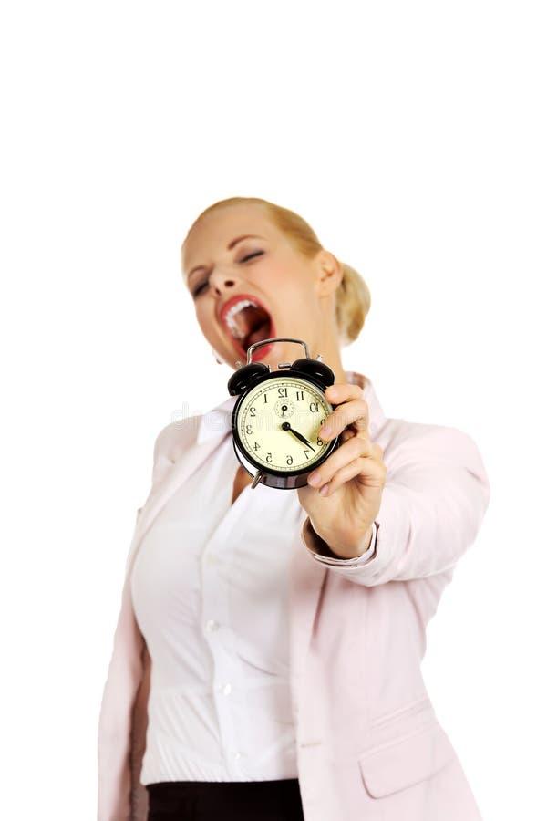 Femme de baîllement d'affaires tenant le réveil image stock