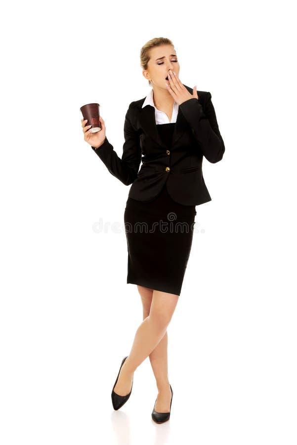 Femme de baîllement fatiguée d'affaires tenant une tasse de café de papier images libres de droits