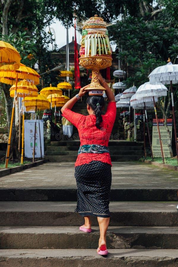 Femme de Balinese dans des vêtements traditionnels portant des offres cérémonieuses sur sa tête photos libres de droits