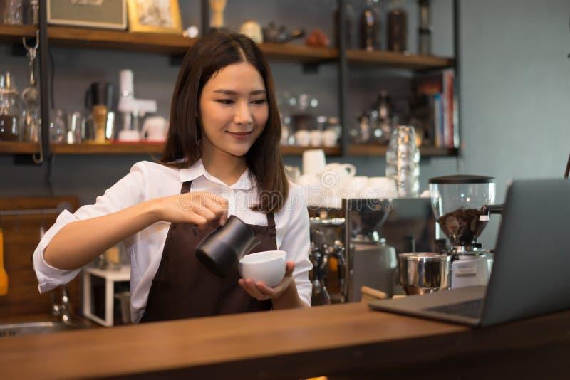 Femme de barman préparant le café d'expresso de brew derrière le compteur photo stock