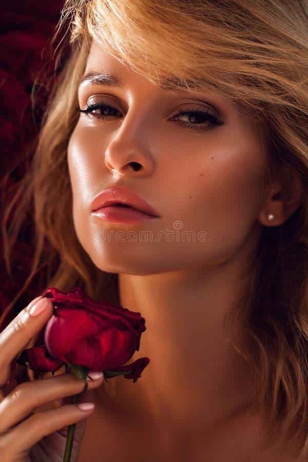 Femme de beauté avec la rose de rouge Façonnez à brune le portrait modèle de visage de fille avec la rose de rouge dans sa main L photo stock