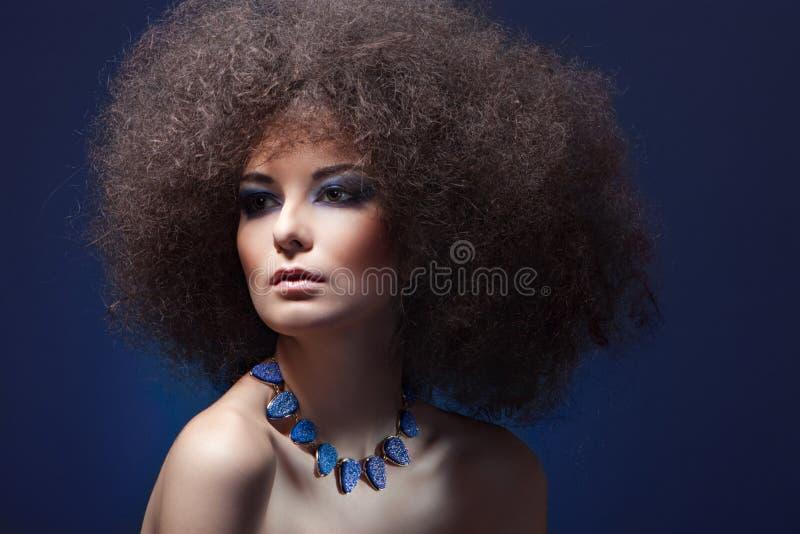 Femme de beauté avec le cheveu bouclé et le renivellement bleu image libre de droits