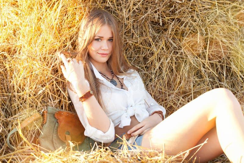 Femme de beauté détendant dans la paille dans le domaine photographie stock libre de droits