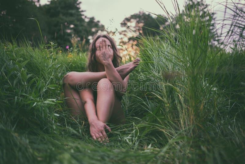 Femme de beauté faisant le yoga avec le visage fermé se reposant dans l'herbe verte La fille hippie de Boho faisant l'asana, appr image stock