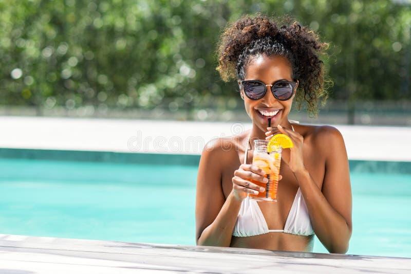 Femme de beauté de mode en cocktail potable de piscine images libres de droits