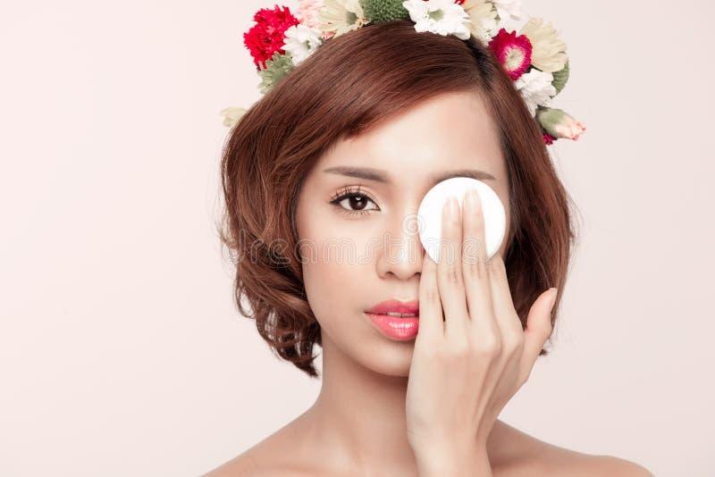 Femme de beauté montrant le tampon de coton sur le visage - l'oeil et les soins de la peau escroquent photographie stock libre de droits