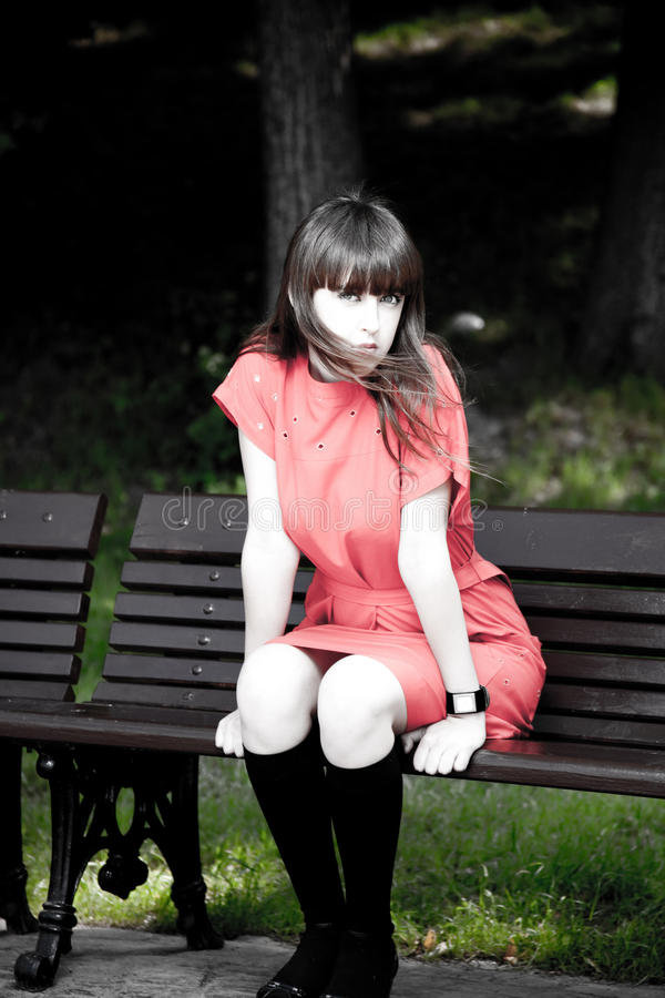 Femme de beauté s'asseyant sur un banc de stationnement photo stock