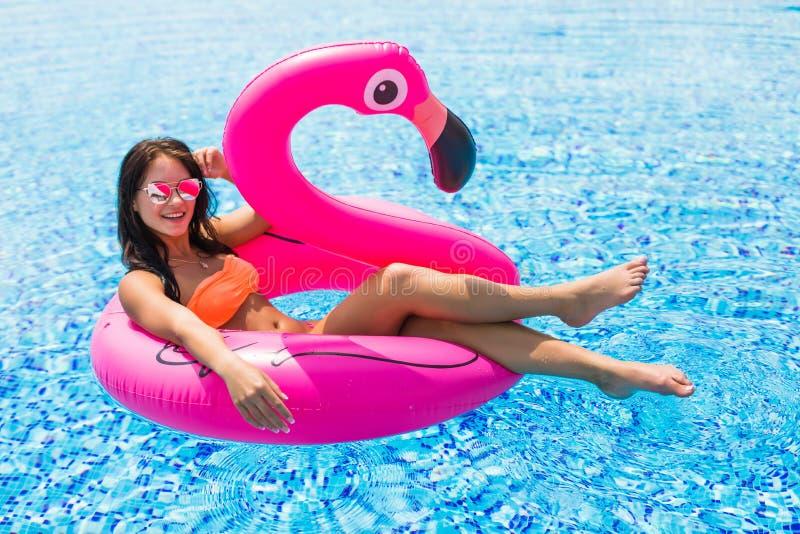 Femme de beauté sur un flamant rose dans la piscine dans des lunettes de soleil photo libre de droits