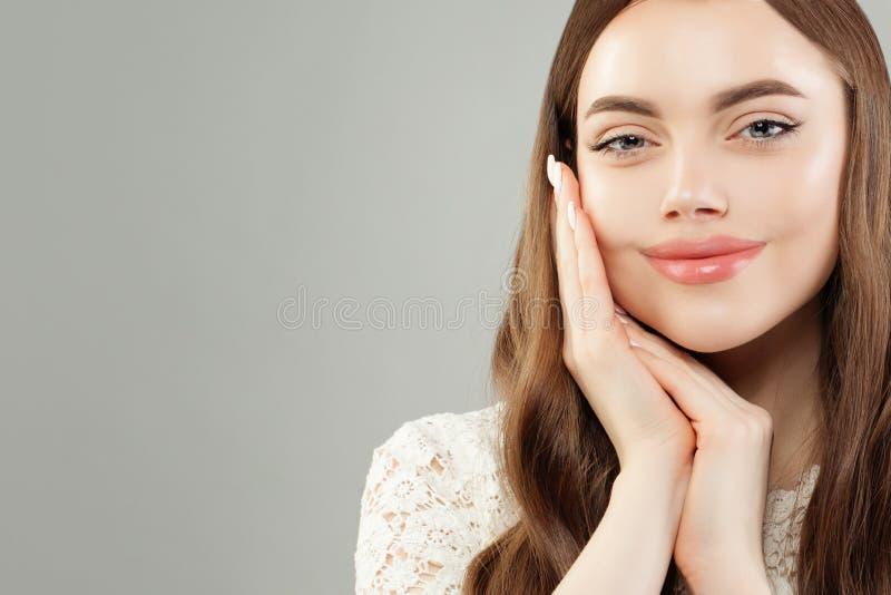 Femme de beaut? avec de longs cheveux boucl?s de Brown Femme mignonne avec la peau claire, les soins de la peau et le concept fac images stock