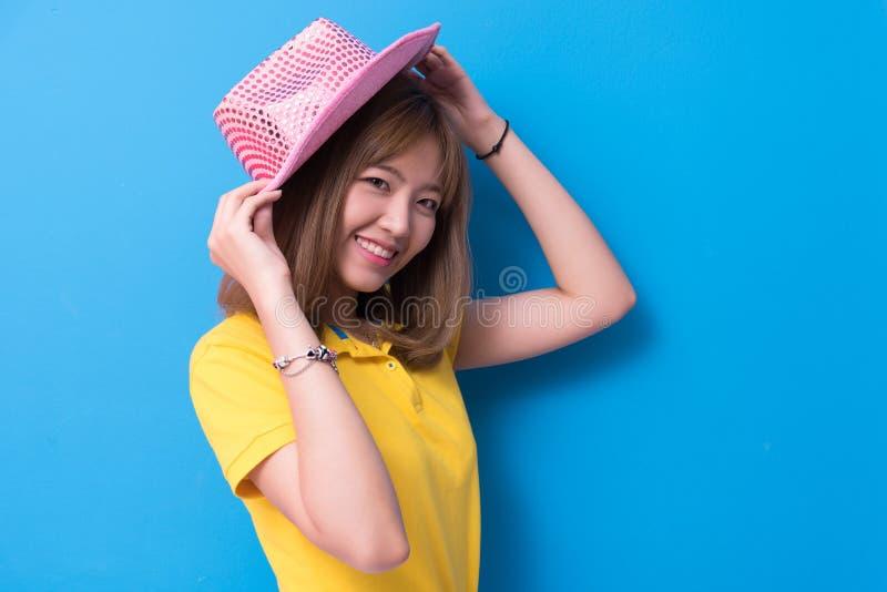 Femme de beaut? posant avec le chapeau rose devant le fond bleu de mur ?t? et concept de vintage Mode de vie et personnes de bonh photo libre de droits
