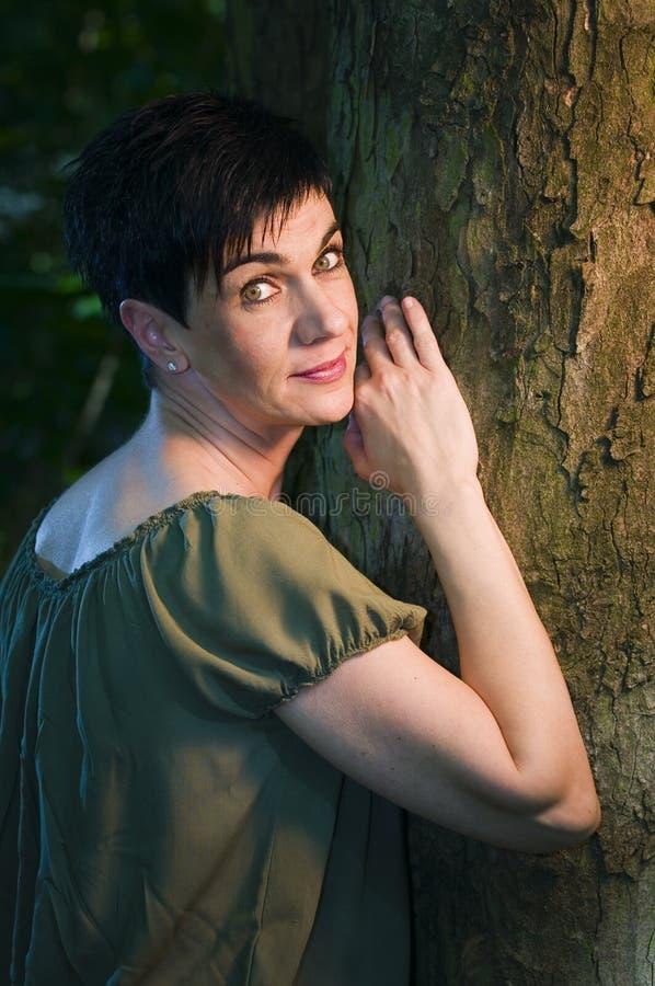 Femme de Beautyful sur un arbre photographie stock libre de droits